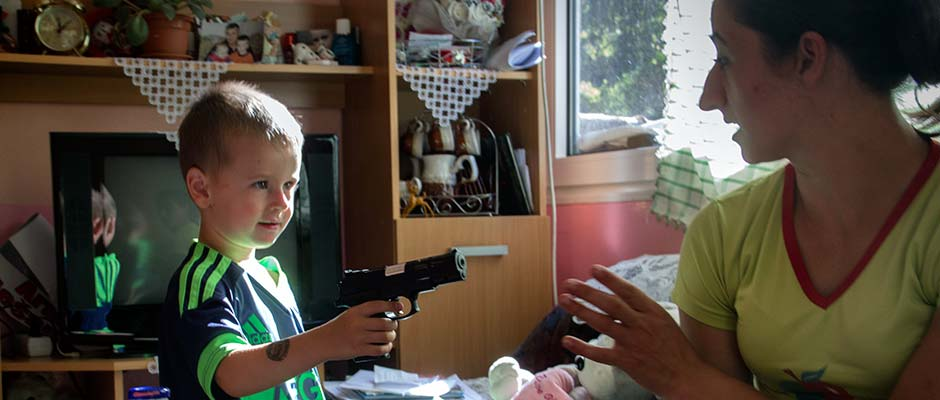 Arman Buljic, at play, points a gun at his mother Admira. | Arman Buljić se igra držeći pištolj uperen u majku Admiru